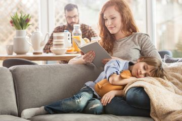 woman reading a book while son sleeping on her lap
